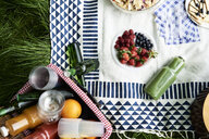 Top view of healthy picnic snacks on a blanket - IGGF00981
