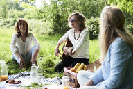 Group of women with guitar having fun at a picnic in park - IGGF01005