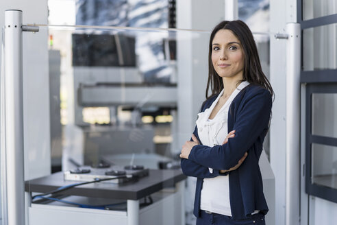 Portrait of smiling businesswoman in a modern factory - DIGF06549