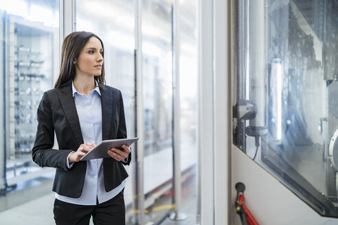 Businesswoman using tablet in a modern factory - DIGF06672