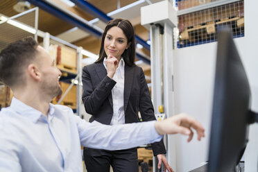 Businessman and businesswoman talking at computer in modern factory - DIGF06699