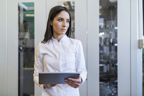 Woman with tablet wearing lab coat in modern factory - DIGF06705
