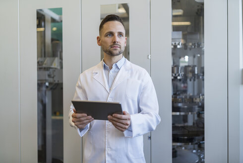 Man with tablet wearing lab coat in modern factory - DIGF06708