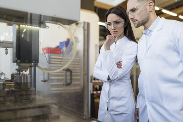 Colleagues wearing lab coats and safety goggles looking at machine in modern factory - DIGF06714