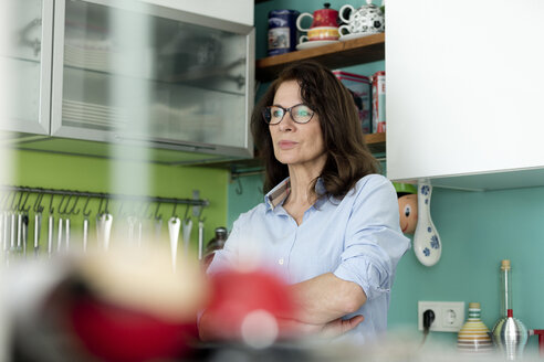 Portrait of pensive mature woman in kitchen at home - FLLF00090