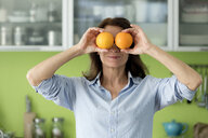 Mature woman covering her eyes with oranges in kitchen at home - FLLF00093