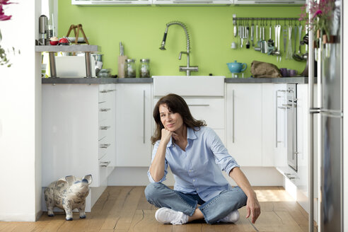 Portrait of mature woman sitting on the floor in kitchen at home - FLLF00096