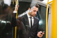 Mid adult businessman on train looking at smartphone - CUF50176