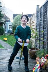 Boy jumping on pogo stick in garden - CUF50203