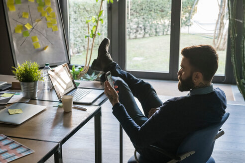 Businessman resting feet on table and using smartphone in office - CUF50212