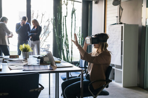 Businesswoman using virtual reality headset in office, colleagues in background - CUF50215