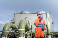 Composite image of worker using walkie talkie in powerstation - CUF50242
