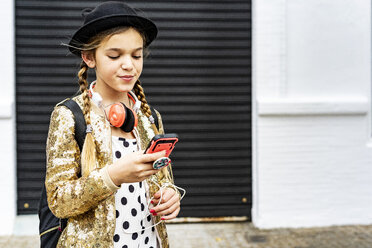 Portrait of girl with headphones wearing hat and golden sequin jacket looking at cell phone - ERRF00893