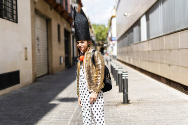 Portrait of girl wearing black crown and golden sequin jacket standing on the street - ERRF00896