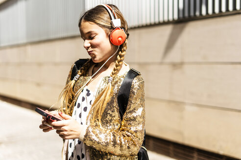 Smiling girl wearing golden sequin jacket and headphones looking at cell phone - ERRF00899