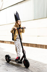 Portrait of smiling girl with E-scooter wearing black crown, golden sequin jacket and polka dot jumpsuit - ERRF00902