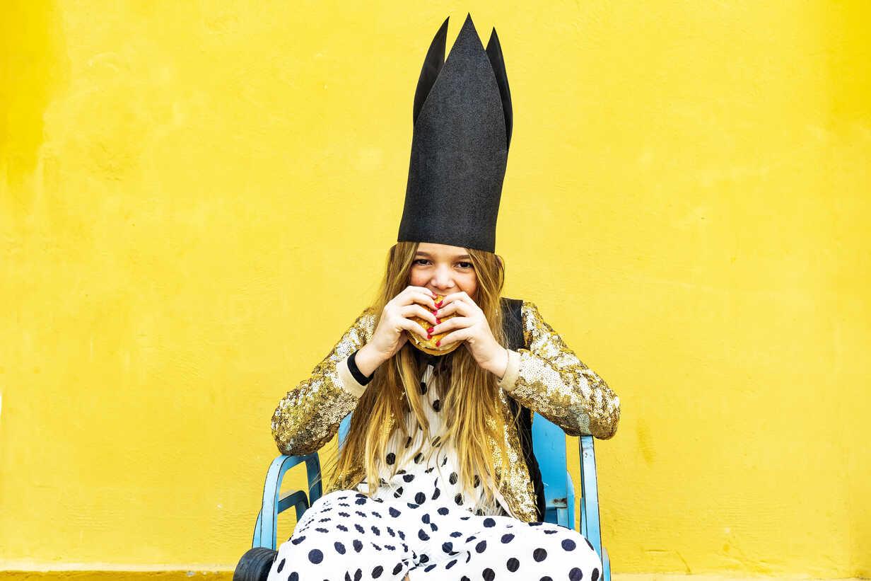 Portrait of girl wearing black crown eating Hamburger - ERRF00911 - Eloisa Ramos/Westend61