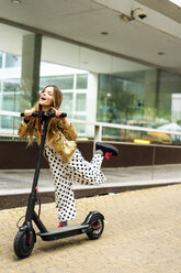 Portrait of laughing girl with E-Scooter wearing golden sequin jacket and polka dot jumpsuit - ERRF00926