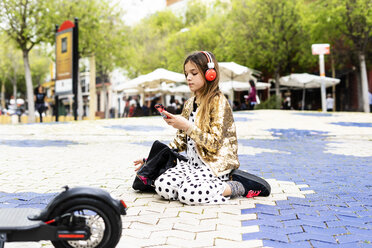 Girl crouching on a square listening music with headphones and smartphone - ERRF00932