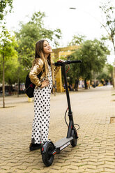 Happy girl with E-Scooter wearing golden sequin jacket and polka dot jumpsuit - ERRF00935