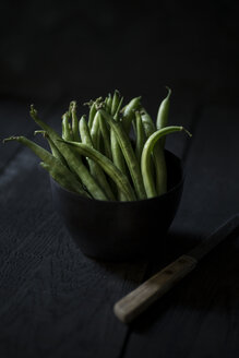Green beans in black bowl on black wood - JESF00234