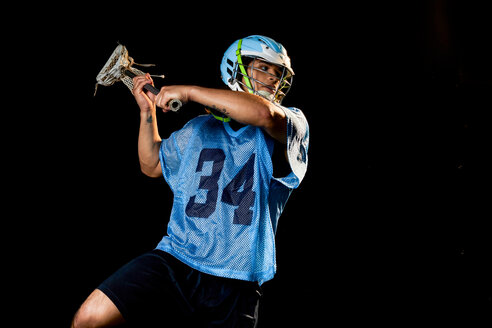 Young male lacrosse player in action with lacrosse stick, against black background - ISF21071