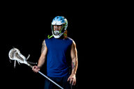 Portrait of lacrosse player, black background - ISF21077