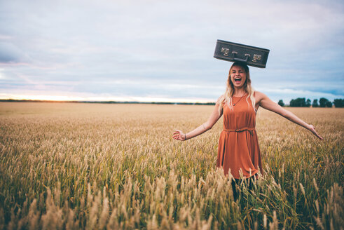 Woman balancing suitcase on head in wheat field, Edmonton, Canada - ISF21089