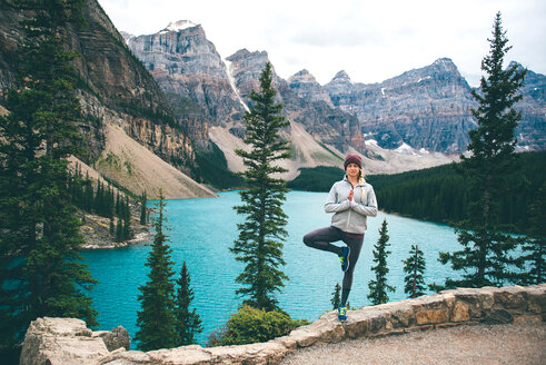 Woman practising yoga, Moraine Lake, Banff, Canada - ISF21098