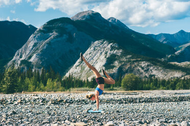 Woman doing handstand on field of stones, Jasper, Canada - ISF21104