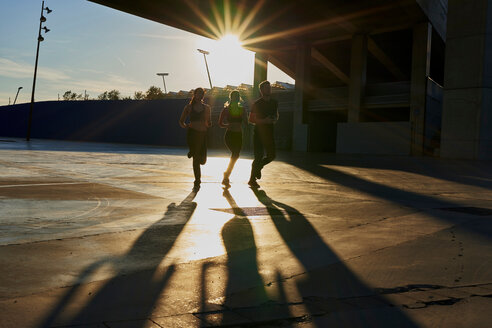 Friends jogging in sports stadium at sunset - CUF50270