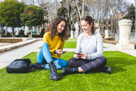 Girlfriends reading message on smartphone in city park, Madrid, Spain - CUF50306