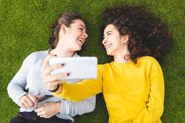 Girlfriends taking selfie on grass - CUF50312
