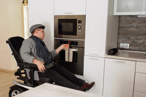 Physically impaired man switching on oven in kitchen - CUF50324