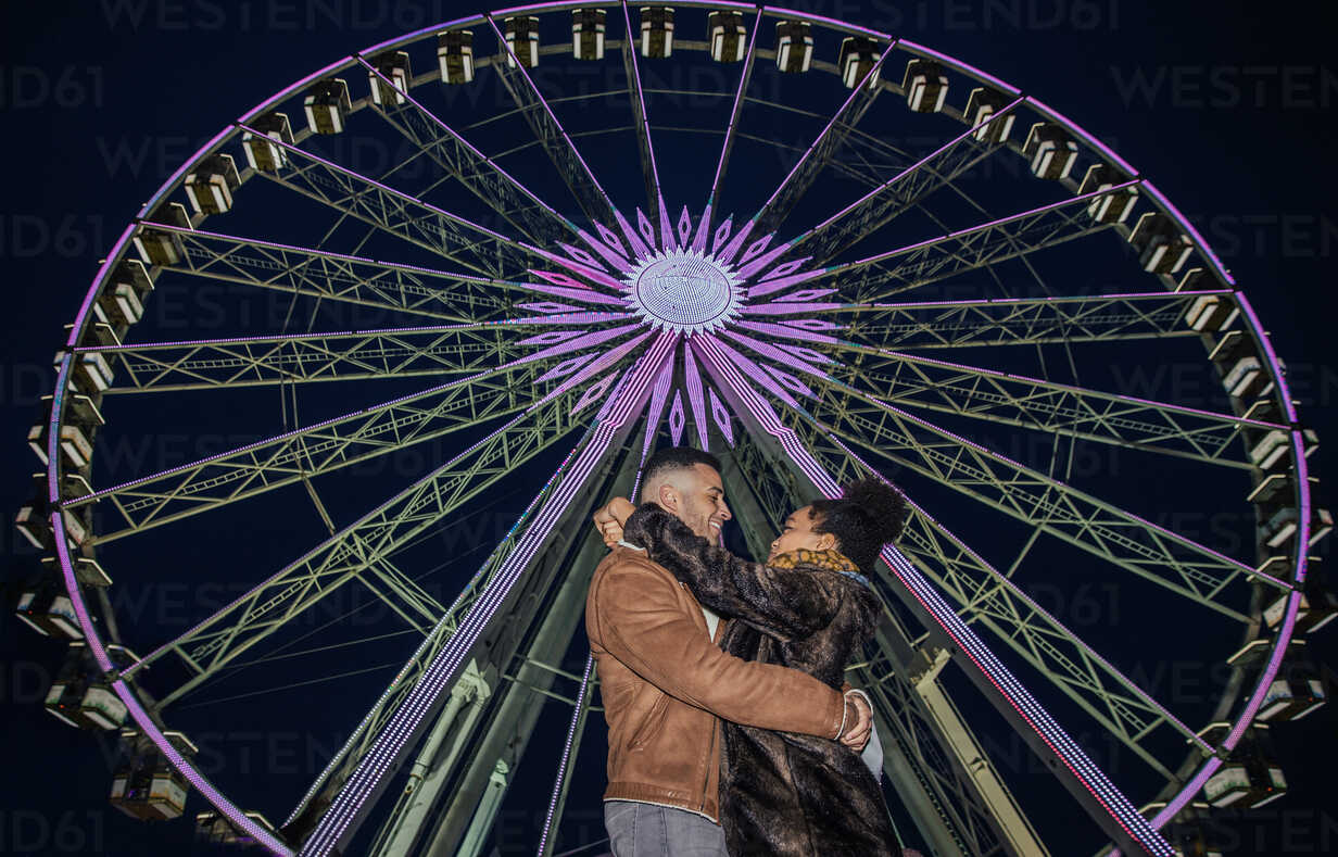 Couple Hugging In Front Of Ferris Wheel At Fairground Cuf50333 Leon Sosra Westend61