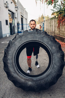 Man with prosthetic leg weight training with giant tyre - CUF50363