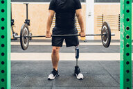 Man with prosthetic leg weight training in gym - CUF50390
