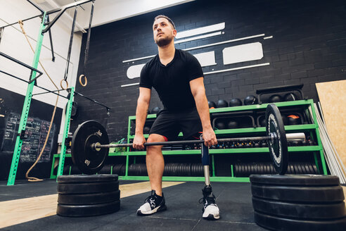 Man with prosthetic leg weight training in gym - CUF50393