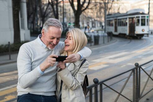 Senior couple using smartphone on sidewalk in city - CUF50426