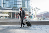 Businessman with wheeled luggage, using smartphone in city centre, Milan, Lombardia, Italy - CUF50465