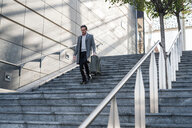 Businessman walking down stairway with wheeled luggage - CUF50468