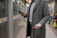 Businessman using smartphone on train platform - CUF50477