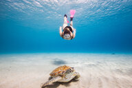 Woman swimming towards green sea turtle, Curacao - CUF50483