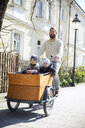 Happy father with two children riding cargo bike in the city - MAEF12832