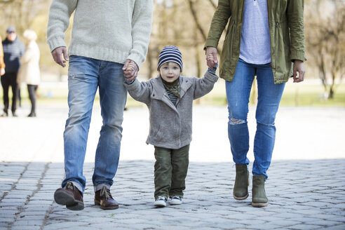 Portrait of boy walking hand in hand with parents - MAEF12835
