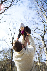 Father lifting up happy daughter in park - MAEF12850
