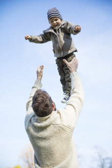 Father throwing happy boy in the air under blue sky - MAEF12853