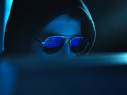 Cyber Crime, reflection in spectacles of virus hacking a computer, close up of face - ABRF00371