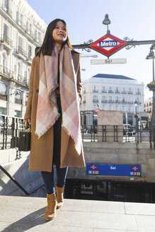 Spain, Madrid, smiling young woman at Puerta del Sol metro station - WPEF01462