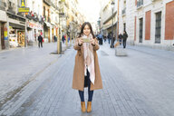 Spain, Madrid, young woman taking photos with a smartphone in the city - WPEF01468